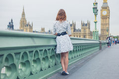 Woman on bridge at houses of parliament. A young woman wearing a white dress is standing on a bridge by the Houses of Parliament in London Stock Photos