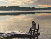 Woman on bridge 2016-12-18 Lindesberg, Sweden. Sad woman sitting on a bridge watching a frozen lake Stock Images