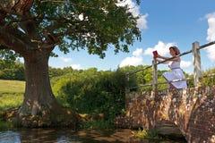 Woman on a bridge reading a book Royalty Free Stock Photos