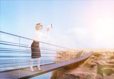 Woman on bridge using megaphone Stock Images