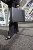 Woman with Briefcase. Close up of a businesswoman's legs and briefcase as she strides through an office lobby. Vertically framed shot royalty free stock photos