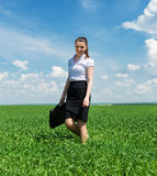 Woman with a briefcase walking on grass Stock Photo