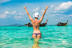 Woman in bright bikini standing in the water with thumbs up Stock Image