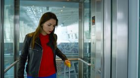 Woman in bright clothes emerges from the elevator at the airport stock video