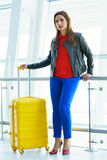 Woman in bright clothes with yellow suitcase stands in the airpo Royalty Free Stock Image