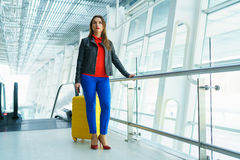 Woman in bright clothes with yellow suitcase stands in the airpo Royalty Free Stock Images