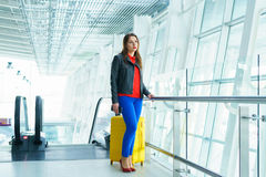 Woman in bright clothes with yellow suitcase stands in the airpo Stock Images