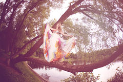 Woman in a bright dress flying in the forest Stock Image