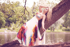 Woman in a bright dress flying in the forest Royalty Free Stock Photography