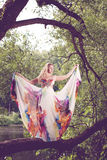 Woman in a bright dress flying in the forest Stock Photos