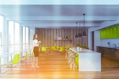 Woman in bright green restaurant interior. Pensive blonde woman standing in modern restaurant interior with white and wooden walls, sofas with bright green stock image