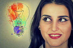 Woman with bright idea light bulb looking sideways Royalty Free Stock Photo