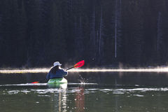 Woman In Bright Kayak On Lake. A woman in a bright kayak on the lake in early morning Stock Images