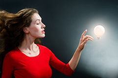 Woman and Bright Light Bulb. Beautiful lady in red with a glowing idea light bulb Royalty Free Stock Image