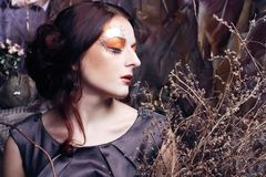 Woman with bright make up with dry branches Royalty Free Stock Photography