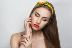 Woman with bright make up. Girl with beautiful makeup, hair and nails. Floral decorations. Hands with long red black nails, neat manicure. Dreaming, thinking Stock Photo