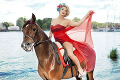 Woman with bright makeup on the horse outdoors Royalty Free Stock Images