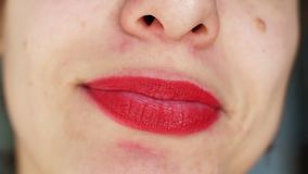 Woman with bright red lips smiles broadly. Close-up stock video