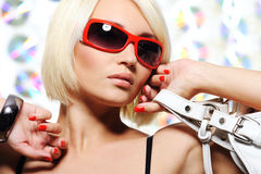 Woman in bright red sunglasses. Portrait of sexy, fashionable and glamour young adult blond woman in bright red sunglasses royalty free stock images