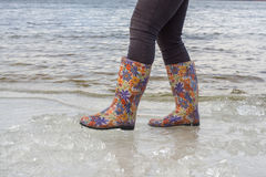 Woman in bright rubber boots walks. Royalty Free Stock Images