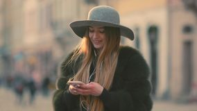 Woman in a bright sunlight uses her phone while standing in the city center. Young woman in a bright sunlight uses her phone while standing in the city center stock video