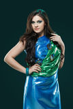Woman in brilliant blue-green dress with peacock feathers design. Creative fantasy makeup, long dark hair. Royalty Free Stock Photo