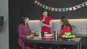Woman bringing champagne to guests at home party. Happy female on occasion of Birthday holiday holding bottle of champagne and putting in bucket with ice in stock video footage