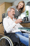 Woman Bringing Man In Wheelchair Hot Drink At Home Royalty Free Stock Photo