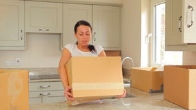 Woman bringing moving boxes into kitchen stock video