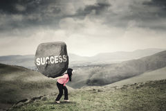 Woman brings boulder with success word Royalty Free Stock Image