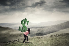 Woman brings dollar sign on mountain. Businesswoman bringing a dollar sign on her bag while walking on the mountain peak royalty free stock photography