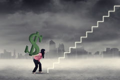 Woman brings dollar symbol on stairway Royalty Free Stock Photography