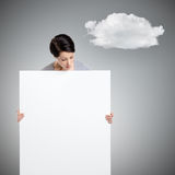 Woman brings a huge sheet of white cardboard. Isolated on grey background with cloud Stock Images