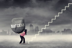 Woman brings stone and climbing stairs. Businesswoman bringing a big stone with Success word on her back and climbing a staircase Stock Image