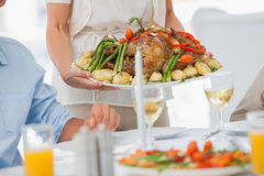 Woman brining a roast chicken in the dining room Stock Photos