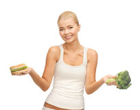 Woman with broccoli and hamburger Royalty Free Stock Image
