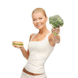 Woman with broccoli and hamburger Stock Photography