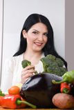 Woman with broccoli and vegetables. Woman in kitchen with many fresh vegetables holding broccoli and smiling.Check out also stock photos