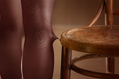 Woman broke stockings. With chair Stock Image