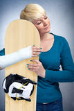 Woman with broken arm hugging her snowboard Stock Photo