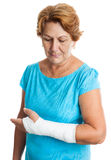 Woman with a broken arm on a plaster cast. Senior hispanic woman with a broken arm on a plaster cast (isolated on white Stock Photo