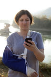 Woman with a broken arm and smart phone Stock Image