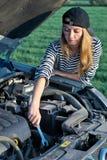 Woman at broken car. Young woman attemting to repair broken car Royalty Free Stock Photography
