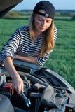Woman at broken car. Young woman attempting to repair broken car Stock Images