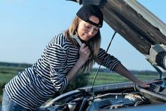 Woman at broken car. Young woman attempting to repair broken car Stock Photo
