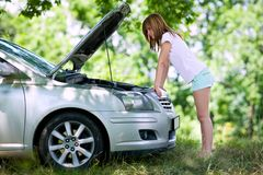 Woman with broken car. Young woman with a broken car in a forest trying to fix it Royalty Free Stock Photography