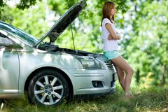 Woman with broken car. Young woman with a broken car in a forest waiting for service Stock Photos