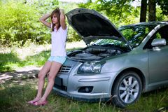 Woman with broken car. Young woman with a broken car in a forest waiting for service Royalty Free Stock Image