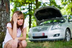 Woman with broken car. Upset woman with a broken car in a forest waiting for help Royalty Free Stock Photo