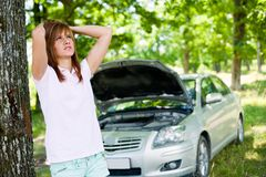 Woman with broken car. Desperate woman with a broken car in a forest waiting for help Royalty Free Stock Image